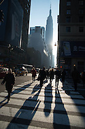 New York Midtown pedestrians going to work at sunrise on 33rd street, the empire state building in the distance / New York pietons partant pur le travail au lever du jour