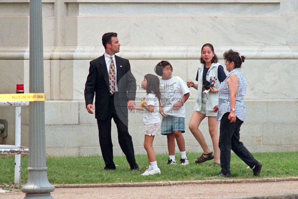Police escort witnesses from the US Capitol after a shooting erupted on Capitol Hill July 24, 1998 in Washington, DC. Two US Capitol police officers were killed in the incident, one person wounded and the lone gunmen was wounded and taken into custody.