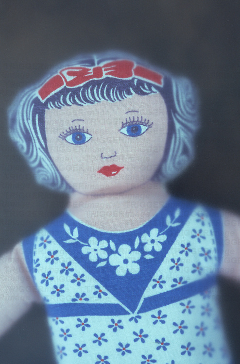 Vintage doll made from cloth or cotton material with face hair and dress all printed in blue red or pink inks behind frosted glass