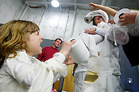 """Katie Dion, 7, takes a moment to enjoy her handiwork at wrapping Connie Johnson in toilet paper during a mummy making competition Friday during """"Egyptian Day"""" at Classical Christian Academy in Post Falls."""