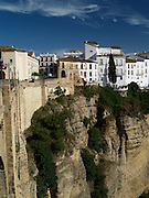 The cliffside city of Ronda, one of the most famous and spectacular towns in Spain. A hangout for Orson Wells and Ernest Hemingway, Ronda is well known for its gorge-straddling bridge (at left) and its bullring. Ronda, Andalusia, Spain.