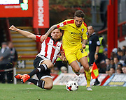 Brentford defender Harlee Dean gets a great challenge in on Rotherham United striker Matt Derbyshire during the Sky Bet Championship match between Brentford and Rotherham United at Griffin Park, London, England on 17 October 2015. Photo by Andy Walter.