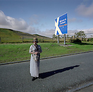 'Tourist, Carter Bar, 2013' from 'A Fine Line - Exploring Scotland's Border with England' by Colin McPherson.<br /> <br /> A Chinese tourist poses for a photograph at a point which historically rival Scottish and English armies would cross the border during skirmishes and battles.<br /> <br /> The project was a one-year exploration of the border between the two historic nations, as seen from the Scottish side of the frontier.<br /> <br /> Colin McPherson is a photographer and visual artist based in north west England. In 2012 he was one of the founding members of Document Scotland, a collective of four Scottish documentary photographers brought together by a common vision to witness and photograph the important and diverse stories within Scotland at one of the most important times in our nation's history.<br /> <br /> 'A Fine Line' will be shown for the first time in public at Impressions Gallery, Bradford, from July 1 until September 27, 2014 to coincide with the Scottish Independence referendum.