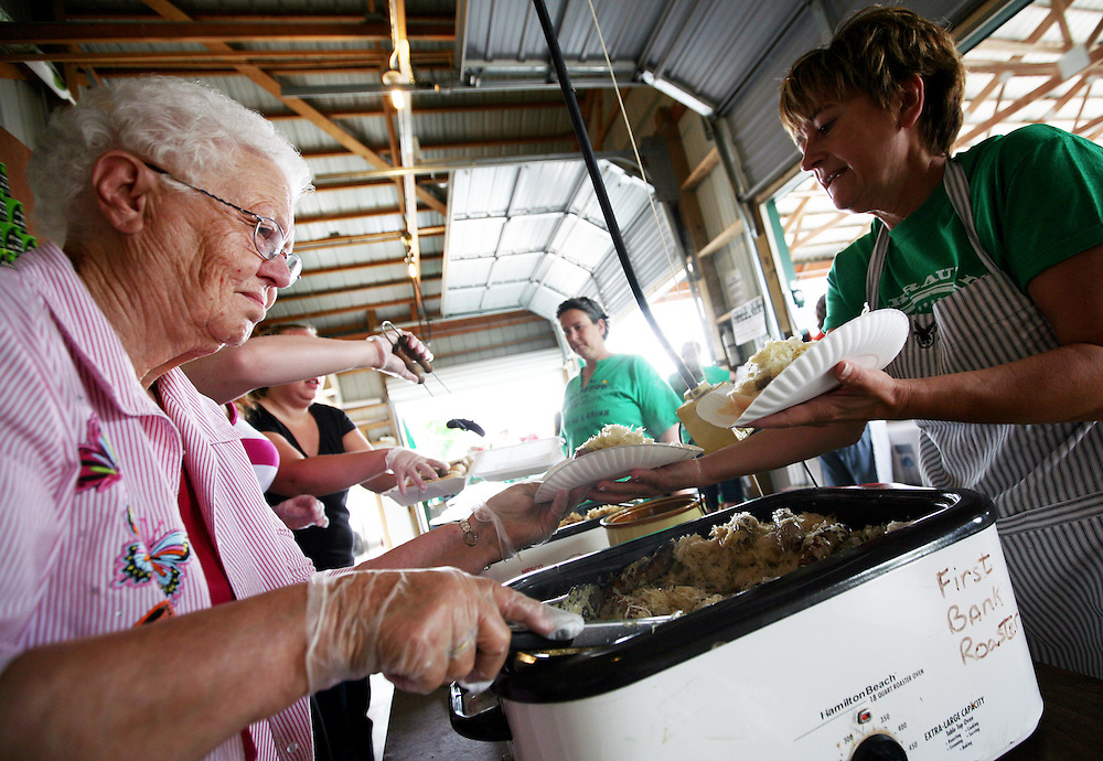 Just as she has done for years, local resident Doris Wigand, left, serves kraut piled onto bratwurst during Sauerkraut Days in Henderson, MN, June 23, 2012.