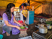 05 AUGUST 2015 - KATHMANDU, NEPAL: A boy watches his mother make breakfast in their tent in a large Internal Displaced Person (IDP) Camp in the center of Kathmandu. The camp is next to one the most expensive international hotels in Kathmandu. More than 7,100 people displaced by the Nepal earthquake in April live in 1,800 tents spread across the space of three football fields. There is no electricity in the camp. International NGOs provide water and dug latrines on the edge of the camp but the domestic waste water, from people doing laundry or dishes, runs between the tents. Most of the ground in the camp is muddy from the running water and frequent rain. Most of the camp's residents come from the mountains in northern Nepal, 8 - 12 hours from Kathmandu. The residents don't get rations or food assistance so every day many of them walk the streets of Kathmandu looking for day work.    PHOTO BY JACK KURTZ