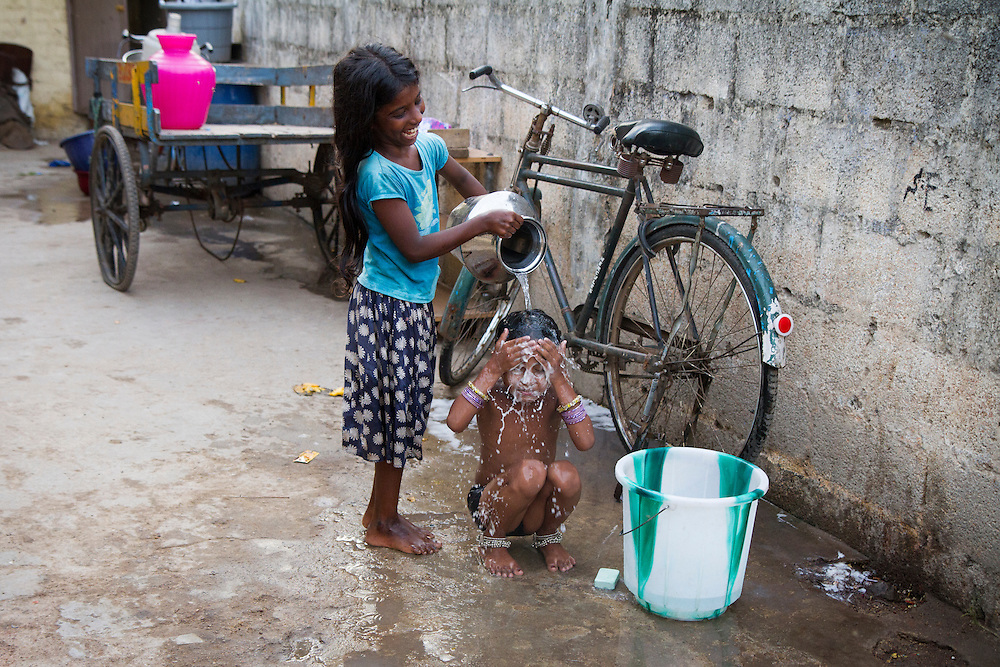 A child helps bathe her younger sister outside their home.  The water in this slum in consistently contaminated and not safe for consumption.