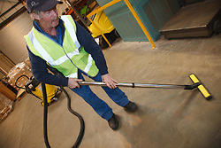 Man with a mild learning disability working as a factory cleaner, shown here hoovering, helped into employment by the Ready 4 Work team, Nottinghamshire County Council