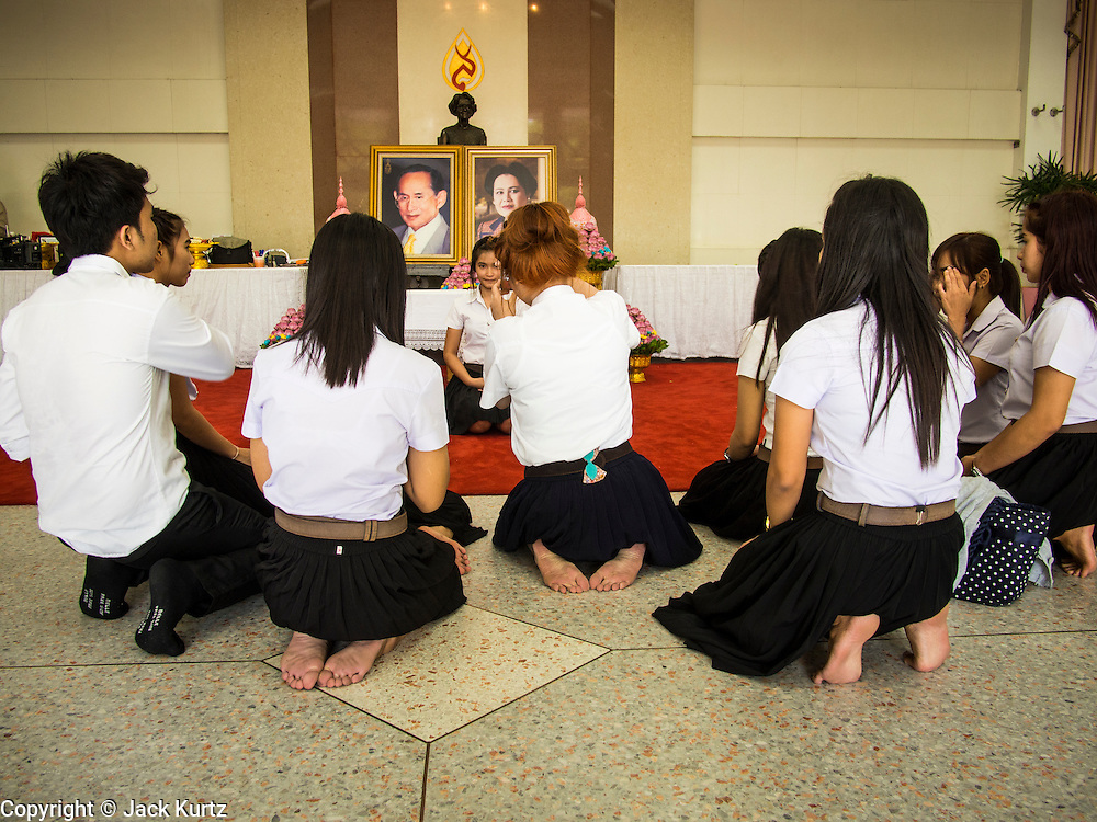 01 AUGUST 2013 - BANGKOK, THAILAND:       Students pray in front of photos of Bhumibol Adulyadej, the King of Thailand, and his wife, Queen Sirikit, who have both been living in Siriraj Hospital. The King, 85, was discharged from the hospital, Thursday where he has lived since September 2009. He traveled to his residence in the seaside town of Hua Hin, about two hours drive south of Bangkok, with his wife, 80-year-old Queen Sirikit, who has also been treated in the hospital for a year.   PHOTO BY JACK KURTZ