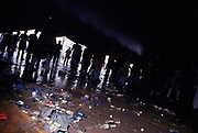 Silhouetted clubbers in a tent litter on the floor at Dance Valley Holland August 2002