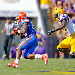 Oct 12, 2013; Baton Rouge, LA, USA; LSU Tigers linebacker Lamin Barrow (18) pursues Florida Gators running back Mack Brown (33) during the first quarter of a game at Tiger Stadium. Mandatory Credit: Derick E. Hingle-USA TODAY Sports