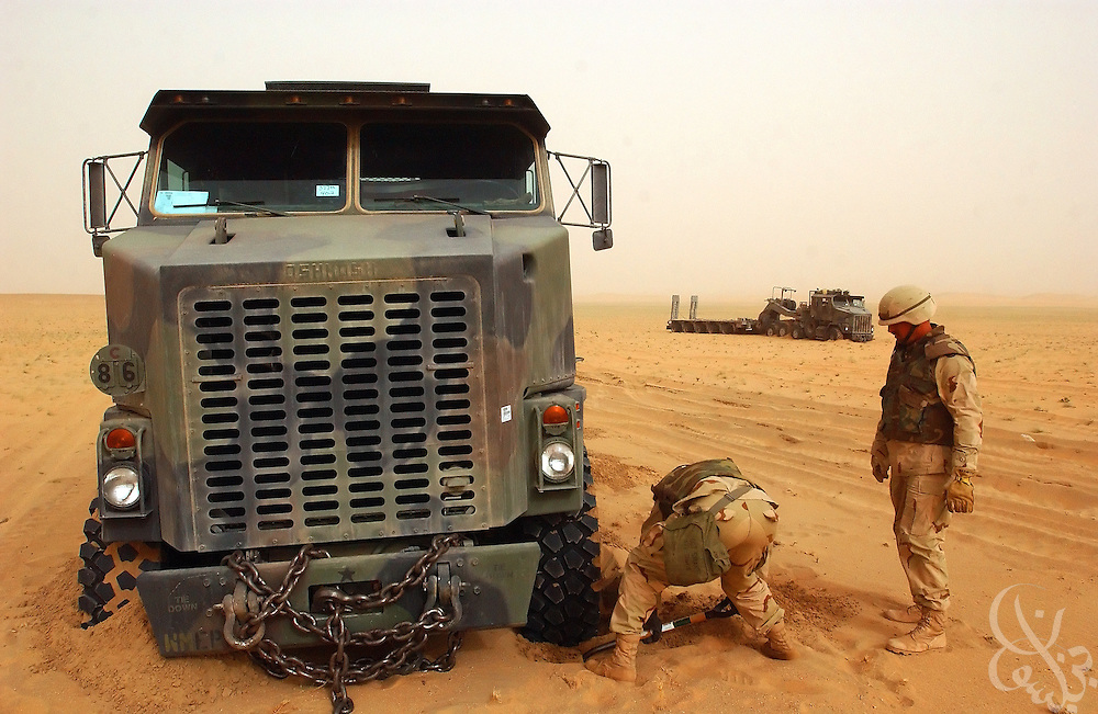 The operator of a U.S. Army 3rd Infantry Division Heavy Equipment Transport Truck (HETT) digs out after becoming stuck in soft sand during a March 19, 2003 pre-invasion manuever in Northern Kuwait. Behind, another HETT also bogs down.