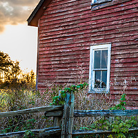 An old red barn and out buildings in autumn sunset.