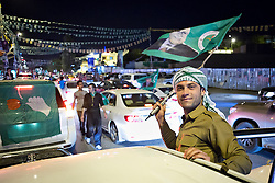 © Licensed to London News Pictures. 27/04/2014. Sulaimaniya, Iraq. A supporter of the Pariotic Union of Kurdistan waves a flag bearing the face of the party's leader Jalal Talabani during celebrations in the lead up to the 2014 Iraqi parliamentary elections in Sulaimaniya, Iraqi-Kurdistan. <br /> <br /> Although banned in other parts of Iraqi-Kurdistan, the days leading up to an election in Sulaimaniya sees political supporters of all the three main parties parading up and down the main street of the city, waving flags, honking horns, letting off fireworks and firing pistols and rifles into the air.<br /> <br /> The period leading up to the elections, the fourth held since the 2003 coalition forces invasion, has already seen six polling stations in central Iraq hit by suicide bombers causing at least 27 deaths. Photo credit: Matt Cetti-Roberts/LNP