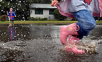 JEROME A. POLLOS/Press..As Tarryn Cherry, 4, makes her way through a puddle in front of her home in Fernan Village, Garrett Dingman, 2, waits to makes his own splash on Wednesday.