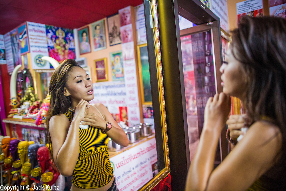 """03 MARCH 2013 - BANGKOK, THAILAND:  KWANT (stage name) a """"coyote dancer"""" from the Never Die dance troupe, dries off and checks her makeup in a mirror after dancing for Chuchok. The troupe usually performs in pubs and at fairs. The Chuchok Shrine is in suburban Bangkok. More than 100 people a week come to the shrine to pray for good fortune or good health. People whose prayers are answered return to the shrine with """"coyote dancers"""" to make merit and thank Chuchok. Coyote dancing is a Thai phenomenon created after the US movie """"Coyote Ugly"""" where attractive young women dance in a sexually suggestive way, usually for pay. They're common at bars and festivals. Coyote dancers are typically better paid than other Thai women in the hospitality industry and usually are not allowed to date or see customers are off the dance floor. Coyote dancers perform at the Chuchok shrine because according to Buddhist literature Chuchok was a relatively repulsive old hermit and Brahmin priest who was cared for by a young woman after he made her family's wishes come true.  PHOTO BY JACK KURTZ"""