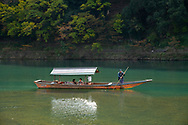 Tourists sightseeing in a small wooden boat on the Oi River in the Arashimaya region out side Kyoto,  Japan