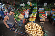A porter carries a large basket of potatoes at the Huembes Market in Managua, Nicaragua