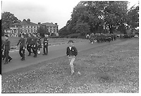 Boy with hands in pockets alongside army cadets marching in step, Blackheath, London street photography in 1982. Tri-X