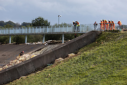 © Licensed to London News Pictures. 05/08/2019. Whaley Bridge, UK. A man wearing climbing kit abseils down the damaged area of the reservoir's slipway as engineers look on . The town of Whaley Bridge in Derbyshire remains evacuated after heavy rain caused damage to the Toddbrook Reservoir , threatening homes and businesses with flooding . Photo credit: Joel Goodman/LNP
