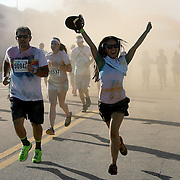 """Participants of the Color Run Orlando event react to getting covered by the colored dust as they attempt to finish the 5K.  Billed as the """"Happiest 5K on the Planet,? the Color Run is a family-friendly run for those who don't mind getting dust thrown at them after beginning the race with a plain white t-shirt on. This is the first event of the season and occured at the Citrus Bowl in downtown Orlando, Florida on January 13, 2013. (AP Photo/Alex Menendez)"""