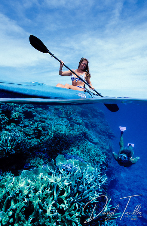 Kayaker watching a woman snorkeller underwater exploring a coral reef in Fiji.