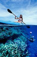 Kayaker watching a woman snorkeller underwater exploring a coral reef in Fiji.