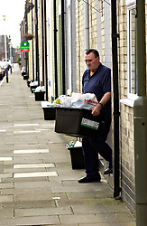 Elderly man putting out his recycling box at his doorstep for collection; Cullercoats Northumberland UK