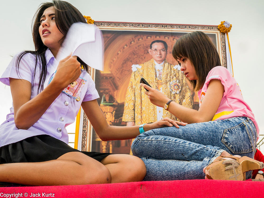 04 DECEMBER 2012 - BANGKOK, THAILAND:  Students from BangkokThonburi University rehearse a play they will put on in honor of Bhumibol Adulyadej, the King of Thailand, whose portrait hangs behind them, at Sanam Luang. The King celebrates his 85th birthday Wednesday, Dec. 5. He is expected to make a rare public appearance and address the nation from Mukkhadej balcony of the Ananta Samakhom Throne Hall in the Royal Plaza. The last time he did so was in 2006. His birthday is a public holiday in Thailand and hundreds of thousands of people are expected to jam the streets around the Royal Plaza and Grand Palace to participate in the festivities.   PHOTO BY JACK KURTZ
