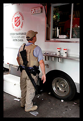 10th Sept, 2005. Hurricane Katrina, New Orleans, Louisiana. A member of the security services waits for hot food served from the Salvation Army truck parked on Canal Street.