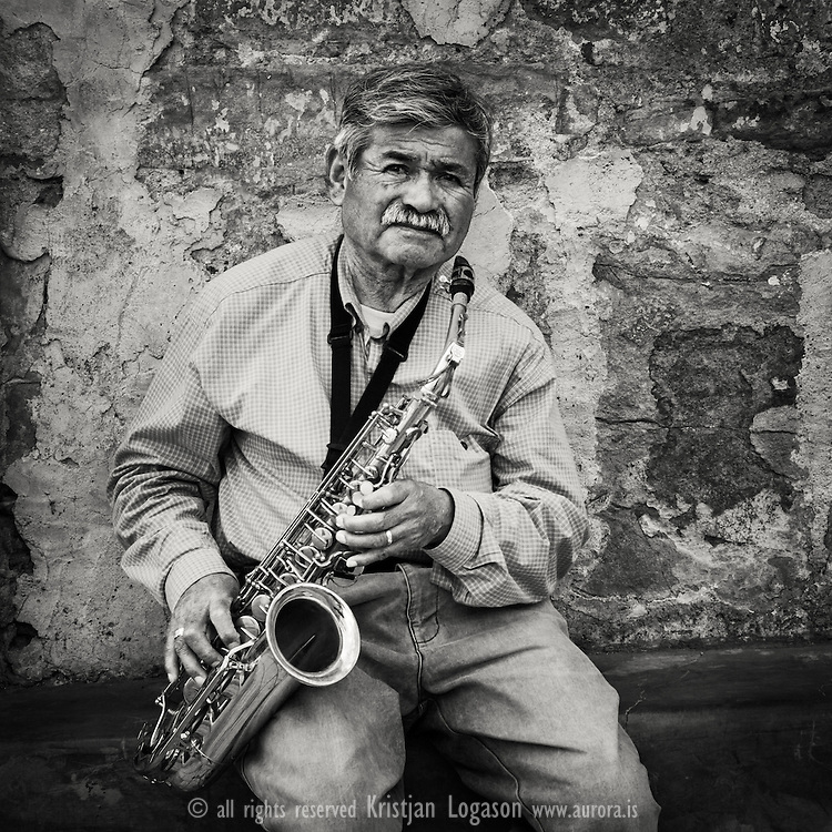 Man in orange shirt playing his saxophone in the streets of Oaxaca