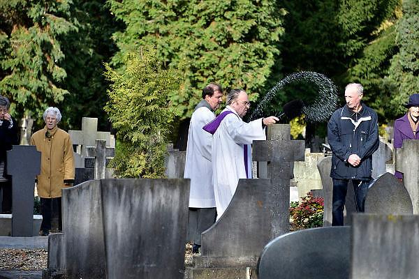 Nederland, Huissen, 3-11-2013Nabestaanden bezoeken een graf op een kerkhof, begraafplaats. De pastoor zegent de graven. Allerzielen, allerheiligen.Foto: Flip Franssen