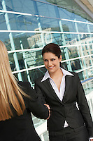 Two businesswomen shaking hands outside of office