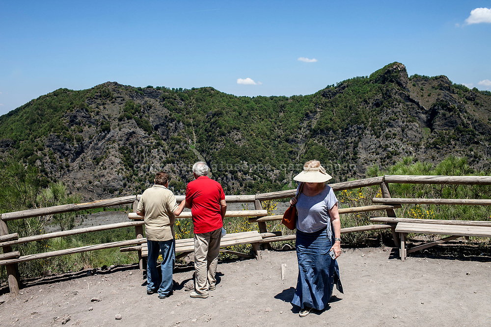 "29 May 2017, Parco Nazionale del Vesuvio, Naples Italy - Tourists on the way for the cone of volcano Vesuvius. Behind the scene the ""Valle dell'Inferno""."