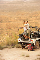 Couple standing in back of four wheel drive car on cliff edge in desert