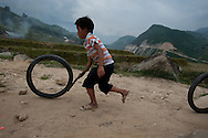 A child plays with a tire and stick making a game out of something so simple with a friend.