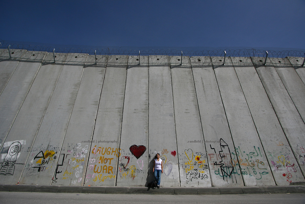 conscientious objector Or Ben David in front of the separation wall in Jerusalem.