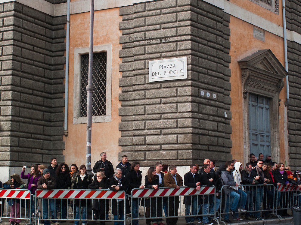 Crowd of people lined up along a barrier in the Piazza del Popolo, Rome; the street sign above their heads on the corner of a building.  The piazza had been cleared for filming a movie scene.