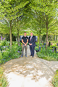 Matthew Keightley and Tom Stimpson   MBE. RAF Veteran on the Hope on the Horizon garden.  The<br /> &lsquo;Hope on the Horizon&rsquo; garden in aid of Help for Heroes: produced by building and landscaping firm Farr and Roberts&rsquo;, making their debut; designed by Matthew Keightley (29), as a result of his brother Michael&rsquo;s involvement with the armed forces, having served on four tours to Afghanistan and due for his fifth this year; and sponsored by the David Brownlow charitable foundation. The garden layout is based on the shape of the Military Cross, the medal awarded for extreme bravery. Granite blocks will represent the soldiers&rsquo; physical wellbeing and the planting represents their psychological wellbeing at various stages of their rehabilitation. Both evolve through the garden from a rough, unfinished, over-grown beginning through to a perfectly sawn, structured end. An avenue of hornbeams draws the attention through the entire garden to a sculpture resembling a hopeful horizon; a reminder to the soldiers that they all have a bright future ahead. As well as areas to recline and reflect, the garden offers focal points all the way through. Cool, calming colours are used throughout, helping to emphasise the fact that it will be a serene, contemplative space. After the Show, the garden will be moved and set within the grounds at Help for Heroes Recovery Centre at Chavasse VC House in Colchester, Essex. The garden will offer a serene, peaceful haven to contemplate and inspire a bright future and to support the challenging journey to recovery. The Chelsea Flower Show 2014. The Royal Hospital, Chelsea, London, UK