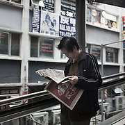 """An early morning commuter travels down the escalators from Mid Levels to Central. <br /> A series of escalators run from the top of the Mid Levels high above the city centre all the way down to the harbor side in Hong Kong Central in the morning bringing thousands of commuters to work. The escaltors change directions at ten am to bring people back up the steep hill the rest ofthe day and night. <br /> <br /> Hong Kong (香港; """"Fragrant Harbour""""), officially known as Hong Kong Special Administrative Region of the People's Republic of China since the hand-over from the United Kingdom in 1997 under the principle of """"one country, two systsems"""".  7 million people live on 1,104km square, making it the most vertivcal city in the world. Hong Kong is one of the world's leading financial centres along side London and New York, it has one of the highest income per capita in the world as well the moste severe income inequality amongst advanced economies. The Hong Kong civil society is highly regulated but has at the same time one of the most lassiez-faire economies with low taxation and free trade. Civil unrest and political dissent is unusual but in 2014 the Umbrella Movenment took to the streets of Hong Kong demanding democracy and universal suffrage. 93 % are ethnic Chinese, mostly Cantonese speaking."""