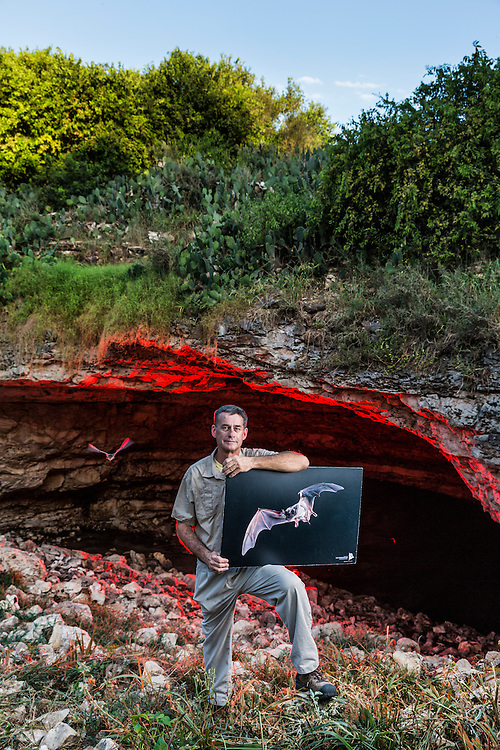 Director of Bat Conservation International's Bracken Cave Preserve, Fran Hutchins monitors the cave and educates vistors on the lives and habits of the Mexican Free-Tailed bat. Here, standing at the mouth of Bracken Cave, Fran holds one of his teaching placards.