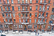 Red brick tenement apartment buildings with fire escapes on Manhattan's East Side in New York City during winter snowstorm.