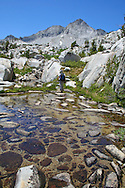 Backpacker steps over rocks in a shallow pool, Sixty Lakes Basin, Kings Canyon National Park