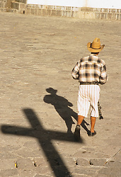 Central America, Guatemala, Antigua, man in traditional clothing walks past shadow of cross