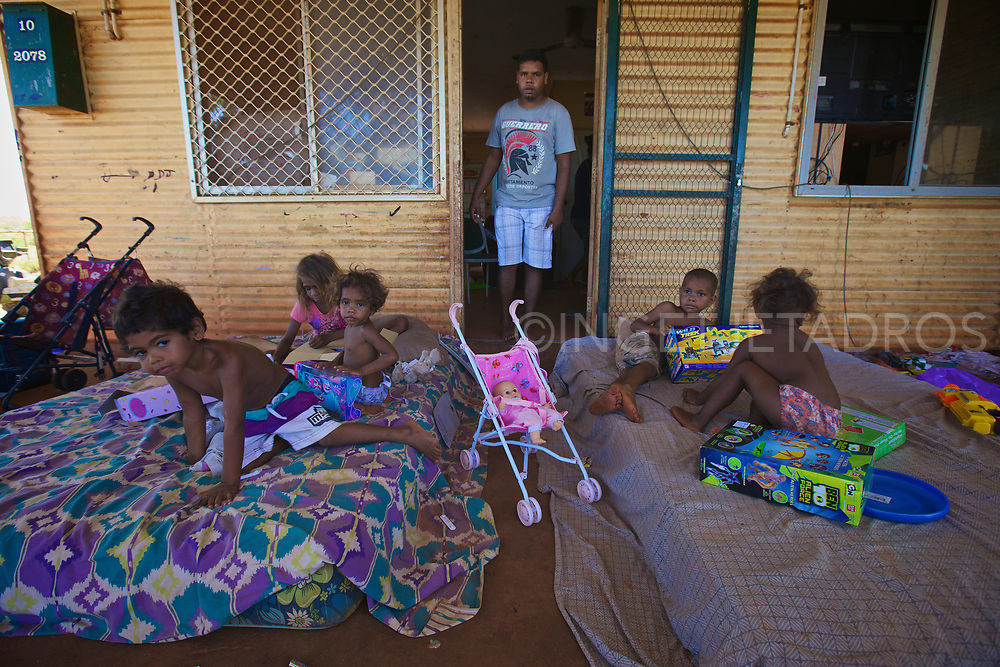 Children unwrapping their presents in front of their home. The Broome Police & Community Centres (PCYC) organise a present drop each year to bring festive spirit to unprivileged children of Broome, WA