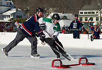 Steve Sanders from PuckNuts and Chris Gallagher from REMax Bayside Hackers battle in front of the goal during first half game action in the Twig division Friday morning during the New England Pond Hockey Classic.  (Karen Bobotas/for the Laconia Daily Sun)