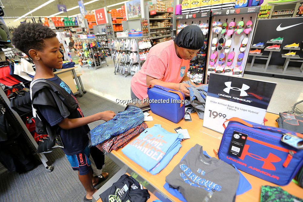 Zykius Richey, 11, of Tupelo, waits as his mother Tinesha looks for him a shirt at Academy Sports Thursday morning in Tupelo. Zykius is one of thirty children from Tupelo Parks and Recreation that received a $100.00 gift card from Academy Sports to go toward their back-to-school shopping.