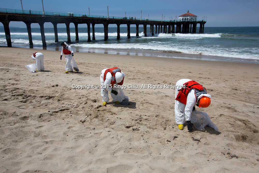 Workers clean up a tar-like substance that washed ashore in Manhattan Beach, California on Thursday, May 28, 2015. Popular beaches along nearly 9 miles of Los Angeles-area coastline are off-limits to surfing and swimming after tar-like substance washed ashore. The beaches along south Santa Monica Bay appeared virtually free of oil Thursday morning after an overnight cleanup, but officials aren't sure if more tar will show up.  (Photo by Ringo Chiu/PHOTOFORMULA.com)