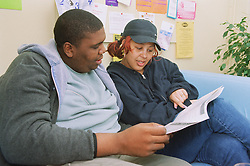 Two clients reading homeless action magazine,