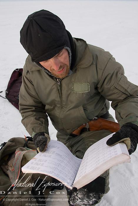 Geoff York, USGS biologist, checks the data base field book that details polar bear captures since 1967 of the Beaufort Sea region. Kaktovik, Alaska.