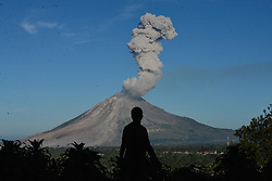 June 15, 2017 - Gundaling, Northern Sumatra, Indonesia -  A person watches Mount Sinabung spewing out volcanic ash in Gundaling village, North Sumatra, Indonesia. Mount Sinabung is one of Indonesia's 129 active volcanoes.  (Credit Image: © Xinhua via ZUMA Wire)